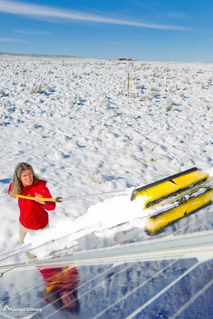 Sweeping new snow off home solar panels Taos New Mexico image