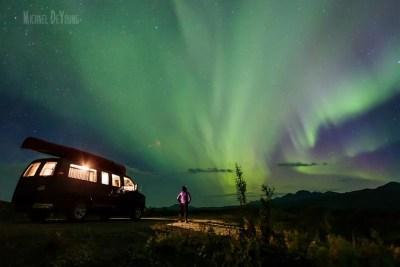 Image of tourist watching aurora dance across the sky along Alaska roadside