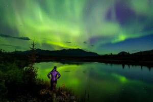 Woman watches aurora display in Alaska