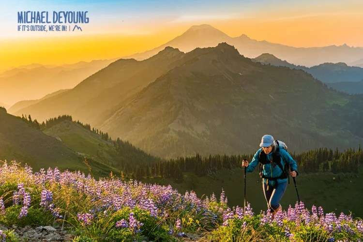 Hiker ascending the Pacific Crest Trail with views of Mt Ranier.