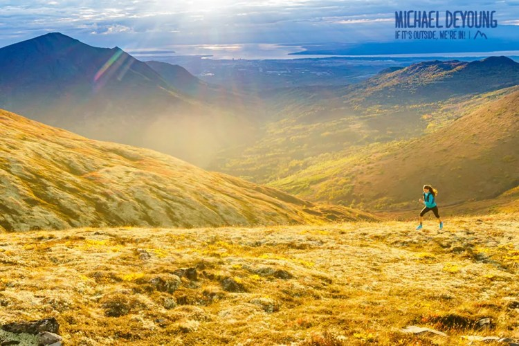 Trail runner running along ridge line with Anchorage below