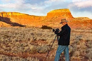 Photographer taking pictures of Redrock cliffs at Ghost Ranch