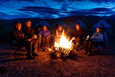 Group enjoy campfire at remote camp. © Michael DeYoung