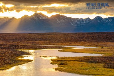 Sunset over the Clearwater Mountains with warm light reflecting off one of the numerous ponds on the tundra of the Denali Highway. © Michael DeYoung