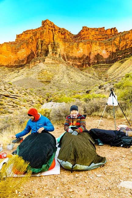 Couple cowboy camping on cold morning in the Grand Canyon. Photo © Michael DeYoung