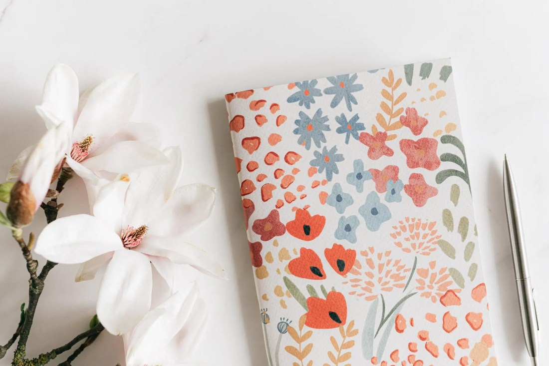 notebook with pen near magnolia flower