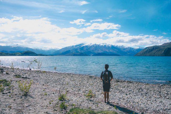 湖の岸辺で立ち尽くす水色のバックパックを背負った短パンの後ろ姿の男性