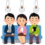 電車の座席に座ってスマートフォンを操作する2人の男性と1人の女性