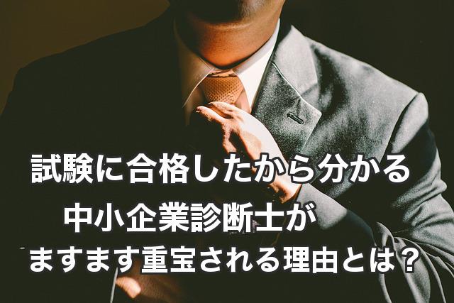 スーツ姿の男性の胸部姿。ネクタイを整える様子。