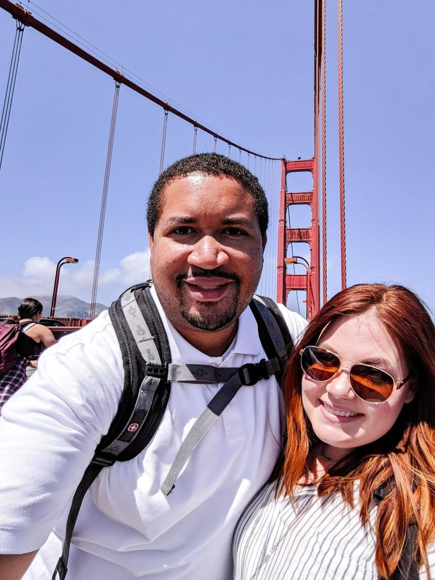 A couple taking a selfie on the Golden Gate bridge.