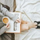 Woman holding a cup of coffee while reading. She has a sweatshirt and socks on