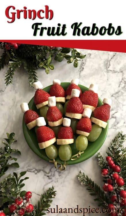 A green plates holds fruit skewers that are inspired by the Grinch. A green grape is skewered with a banana slice then a strawberry and mini marshmallow to represent a Santa hat.