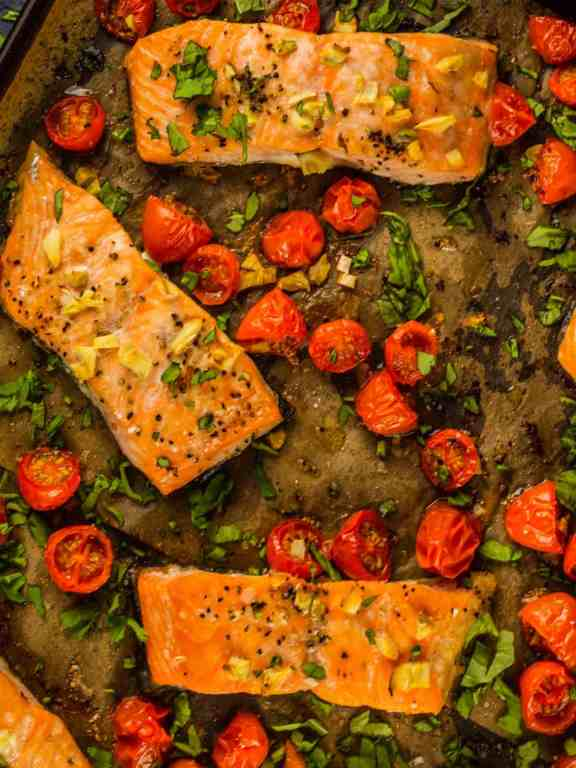 Roasted salmon fillets sit on top of parchment paper, along with cherry tomatoes, minced garlic, and topped with fresh basil.