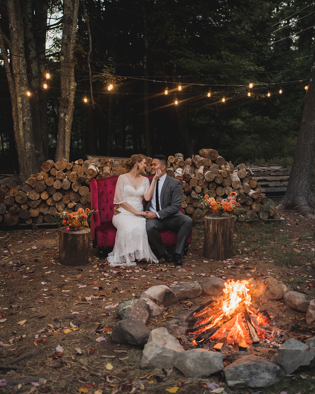bride and groom sitting outside by fire