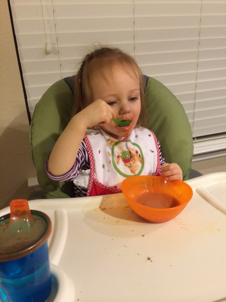 Eliza eating tomato soup with her spoon