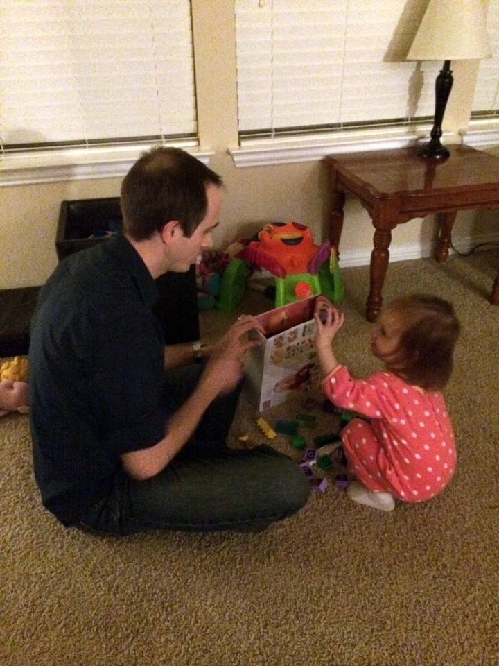 Eliza and Daddy cleaning up the toys.