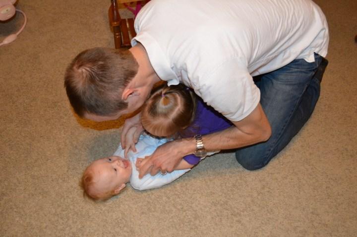 Adam and Eliza tickling James.
