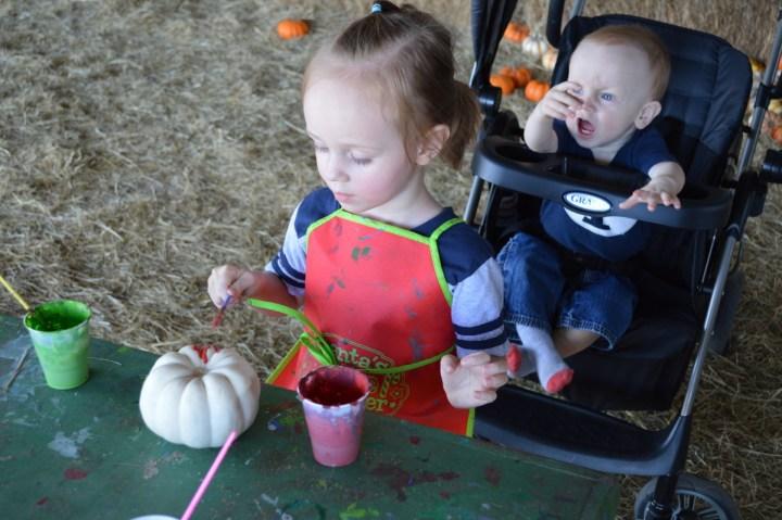 Eliza painting her pumpkin.