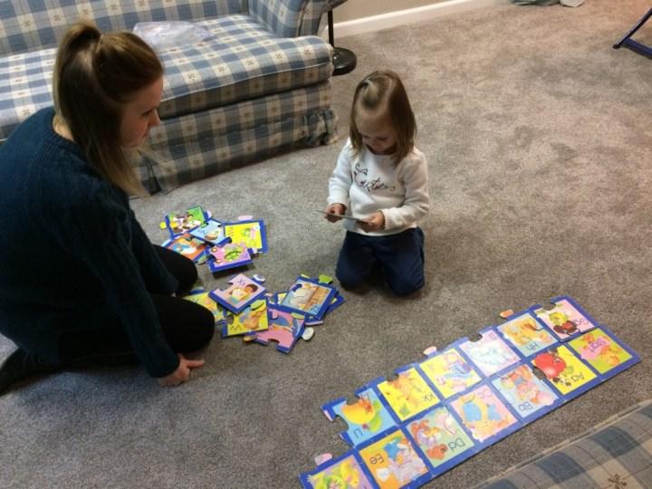 Aunt Beka helped Eliza put together an old alphabet puzzle.