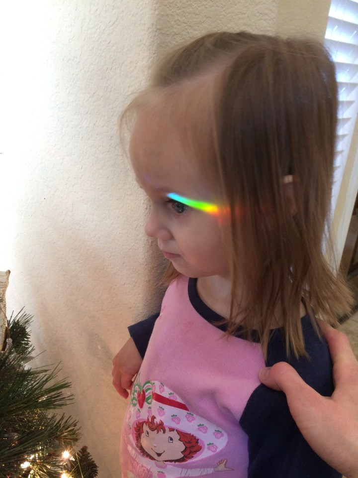 Eliza with a rainbow on her face from the crystal ornaments on the tree.