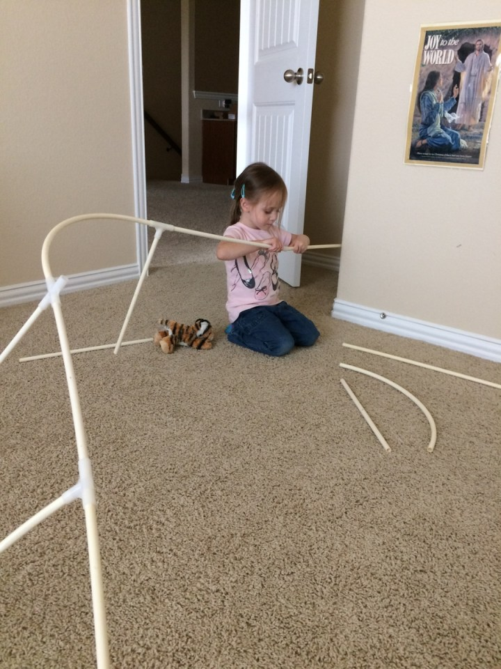 Eliza making a dragon from the poles for her tent.