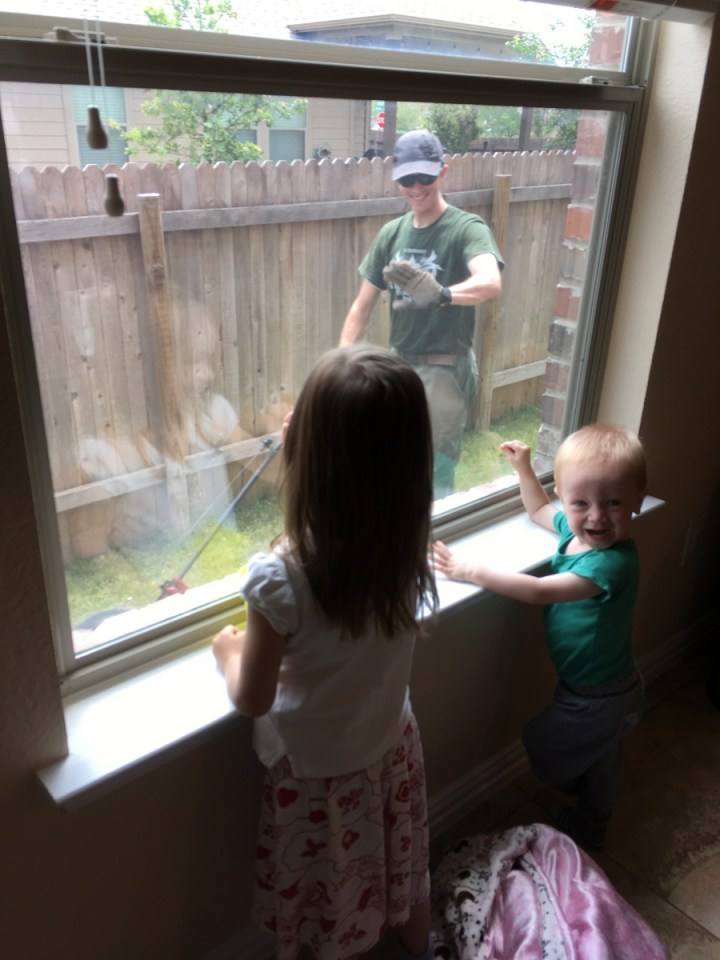 Eliza and James watching daddy mow the lawn.