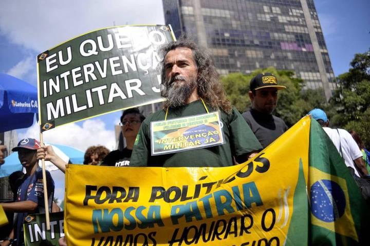 "Protest sign reads ""Eu Quero Intervencao Militar Ja"""
