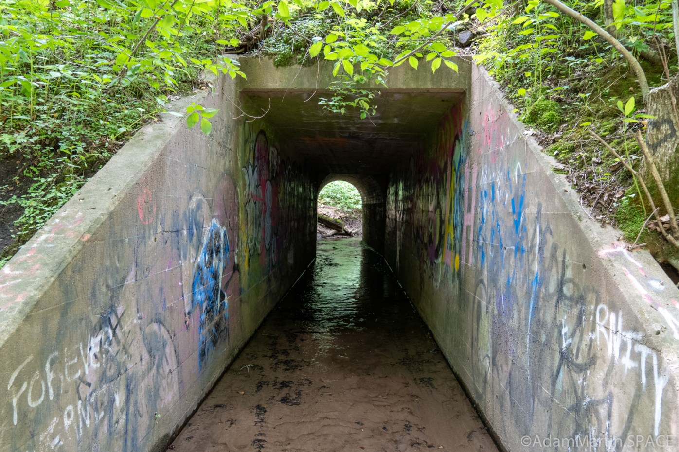 Devil's Punchbowl - Tunnel with graffiti above the falls