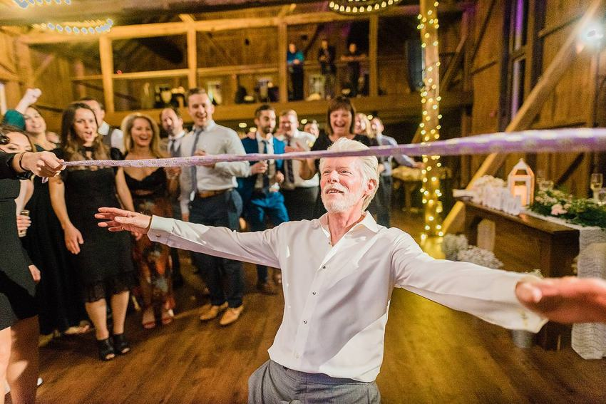 father of groom doing limbo at wyndridge farm wedding by Washington DC Wedding Photographer Adam Mason