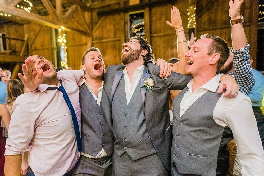 groom and groomsmen laughing and singing at wyndridge farm wedding