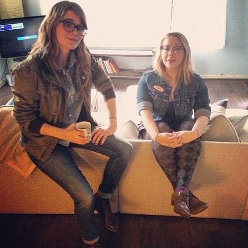 Jenny Owen Youngs and Julia Nunes on a yellow couch.