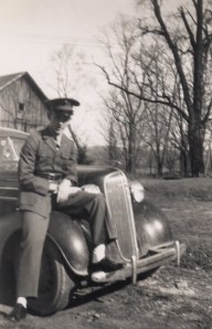 Pfc Robert Benson sitting on the fender of Dad's 1936 Chevy in 1946