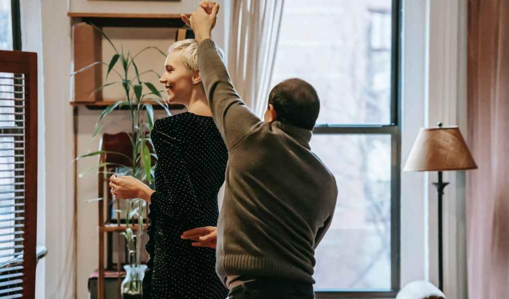 smiling couple dancing in room near window