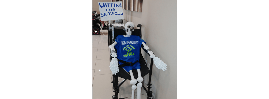"""Skeleton on a wheelchair with a sign that reads """"Waiting for services"""""""