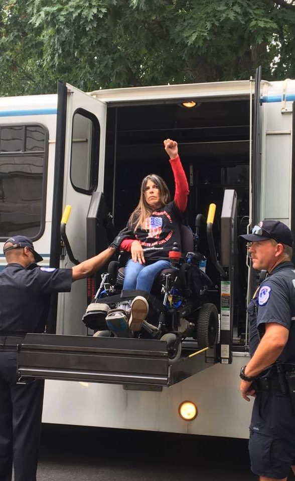 In her wheelchair on the lift of a wheelchair accessible police van with fist raised in a power position.