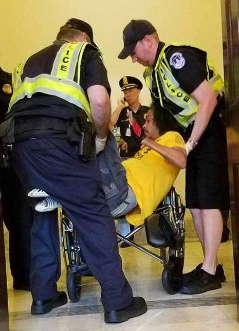 Being lifted from the floor by police officers to remove him from office