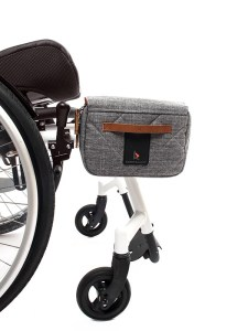 Kinetic Balance Rack Pack, a grey bag with brown leather trimmings, clipped to the frame of a white manual wheelchair.