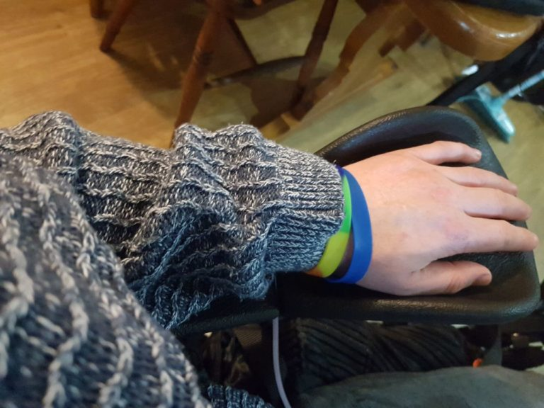 My arm in a blue jumper, with my hand spread out on a black pad.