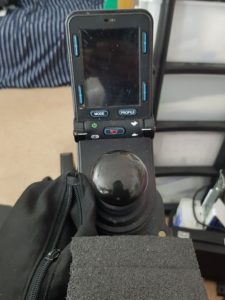 The centre of the image is a mushroom shaped joystick. Above it is a black screen, switched off. Below the wheelchair joystick is some black foam and a black bag.