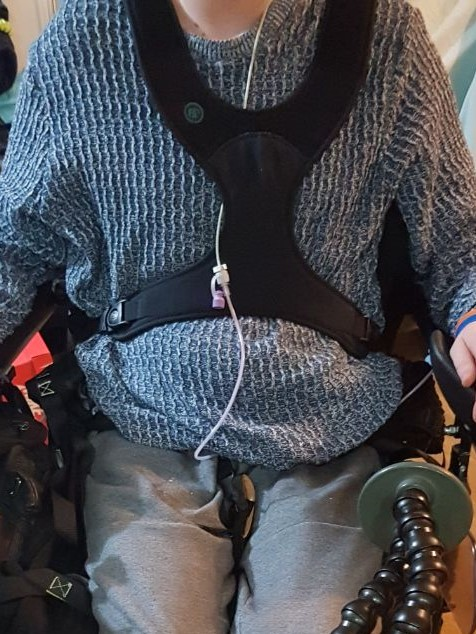 The image shows my upper body in a blue jumper, with a 4 point black harness over me, securing me at the shoulders and hips. My feeding tube is dangling.