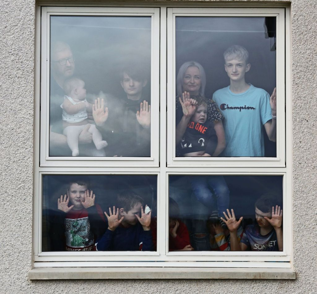 A family of 9 standing by a window
