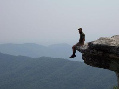 Backpacker sitting on the edge of a cliff