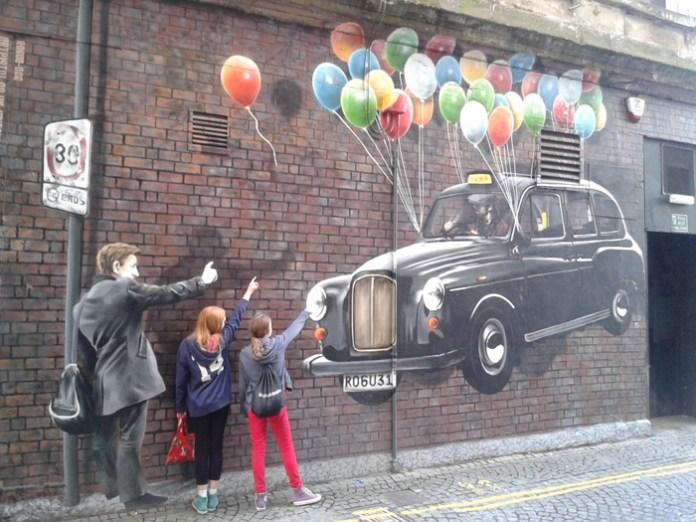 Children pose in front of Art Pistol work.