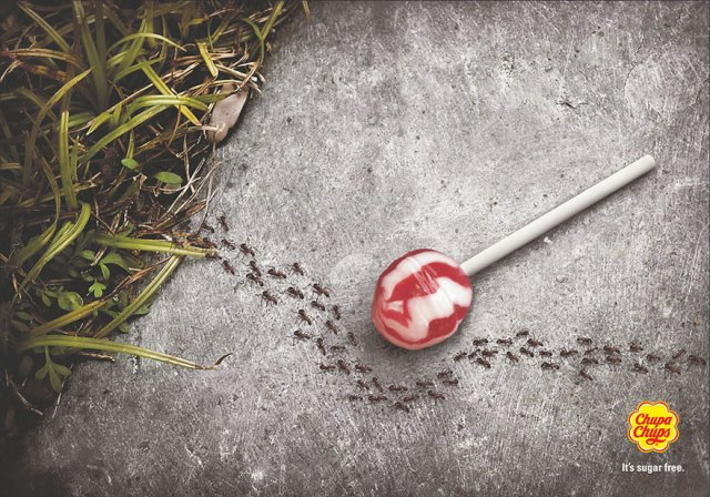 Cupa Chups ad of sugar free lollipop on floor with ants going around it.