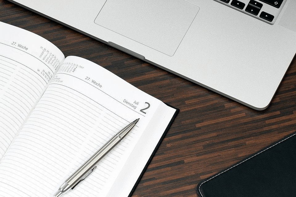 A laptop open with a notebook and pen for planning
