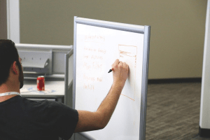 Writing goals on a whiteboard during a meeting