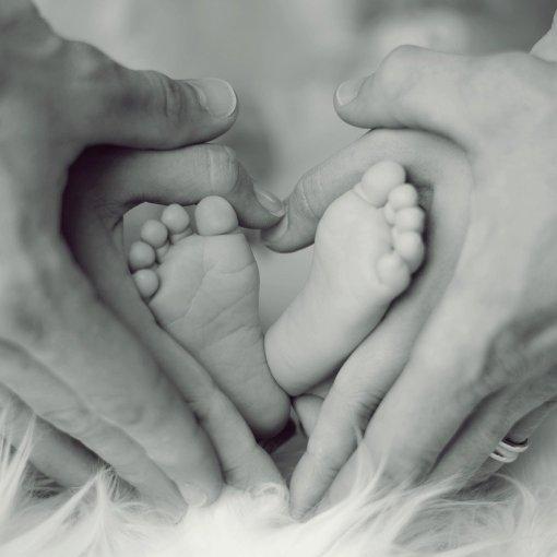 Imagen de unas manos adultas en torno a los pies de un bebe