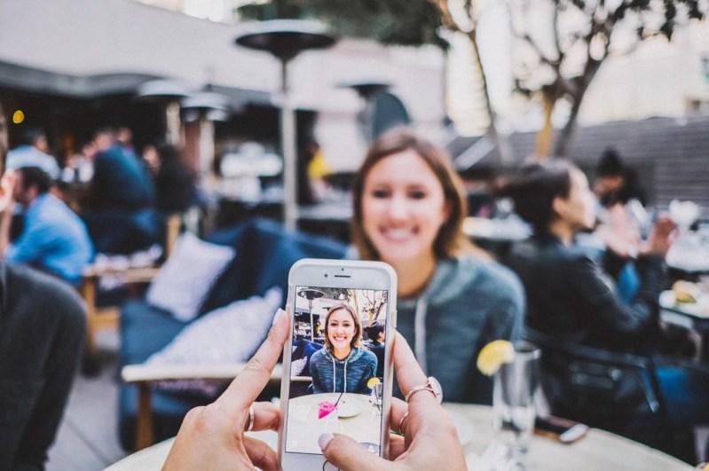 Imagen de una persona subiendo una fotografía de otra a las redes sociales