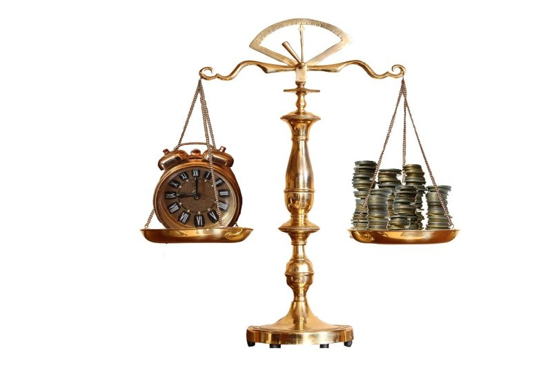 Balanza con dinero y un reloj en cada extremo