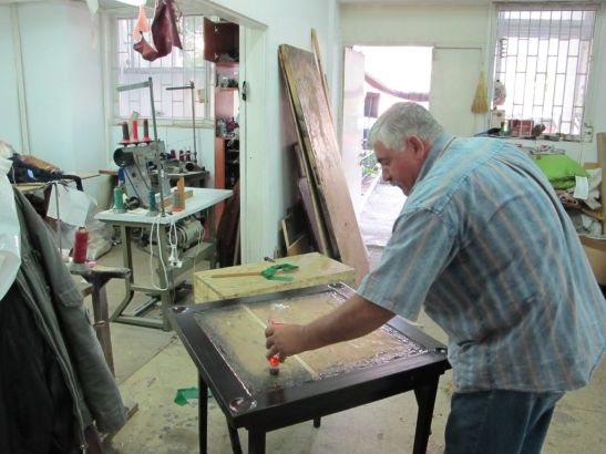 Tapiterul Marian Vasile reconditiona o masa veche ce urma sa fieimbracata cu catifea